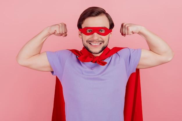 Foto van jonge opgewonden superman gelukkige positieve glimlach toont handen spieren sterk geïsoleerd over roze kleur achtergrond