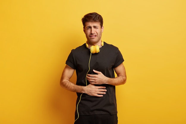 Foto van jonge overstuur europese man lijdt aan buikpijn, houdt beide handen op de buik