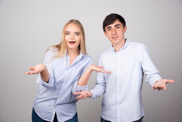 Foto van jonge paar man en vrouw schouders ophalen met open handpalmen.