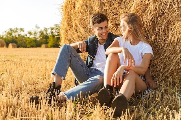 Foto van jonge paar man en vrouw zitten onder grote hooiberg in gouden veld, tijdens zonnige dag