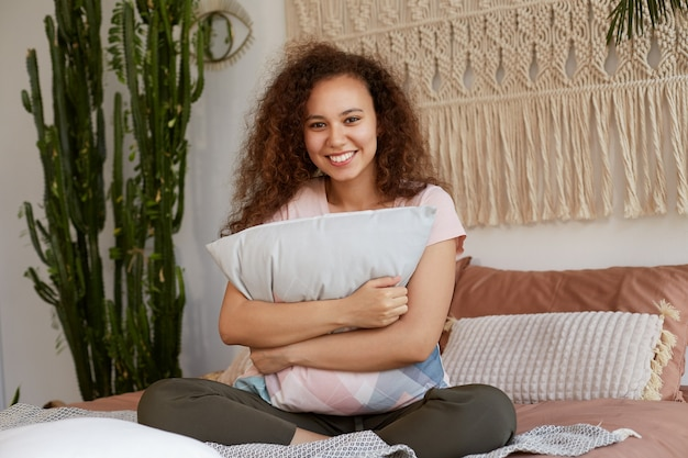 Foto van jonge positieve donkere vrouw met krullend haar, zit op een bed en knuffelt een kussen, glimlacht breed en kijkt naar de camera, ziet er gelukkig en opgewekt uit.