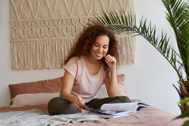 Foto van jonge positieve donkere vrouw met krullend haar, zit op het bed en leest een nieuw nummer van favoriete tijdschrift, geniet van zonnige vrije dag.