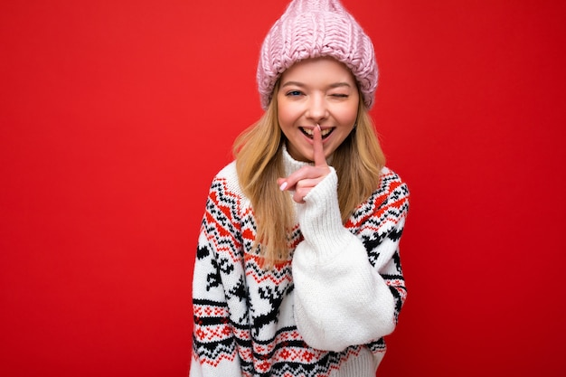 Foto van jonge positieve gelukkige mooie blonde dame met oprechte emoties roze gebreide muts dragen