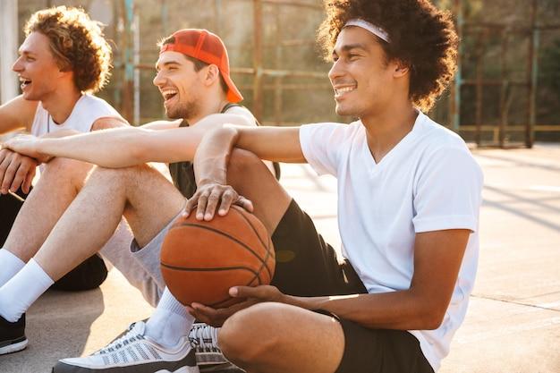 Foto van jonge professionele basketbalspelers zittend op speelplaats buiten, en kijken naar spel tijdens zonnige zomerdag