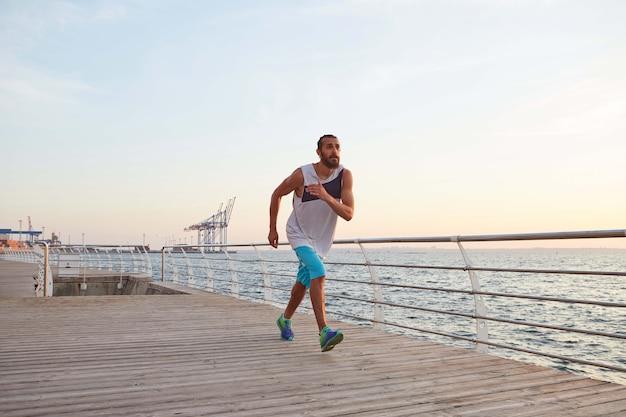 Foto van jonge sportieve bebaarde man aan de kust die ochtendrun doet, ziet er goed uit.