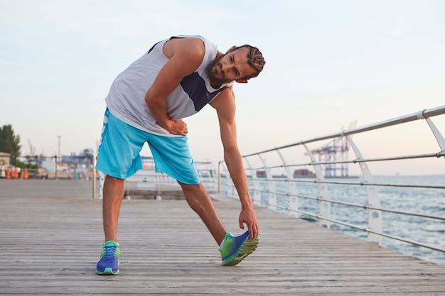 Foto van jonge sportieve bebaarde man die zich uitstrekt, ochtendgymnastiek doet aan zee, warming-up na het hardlopen.