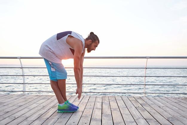 Foto van jonge sportieve bebaarde man die zich uitstrekt, ochtendgymnastiek doet aan zee.