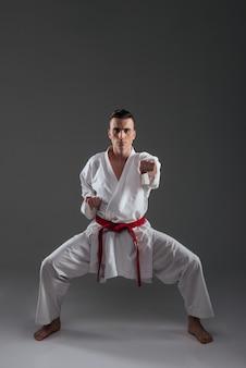 Foto van jonge sportman gekleed in kimono praktijk in karate geïsoleerd over grijze achtergrond. camera kijken.