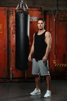 Foto van jonge sterke bokser die traint in een sportschool. camera kijken.