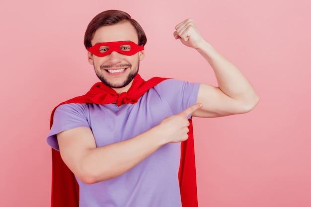 Foto van jonge superman gelukkig positief glimlach punt vinger handen spieren sterk geïsoleerd over roze kleur achtergrond