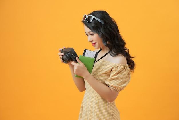 Foto van jonge toeristendame met camera die over het gele paspoort van de muurholding met kaartjes wordt geïsoleerd