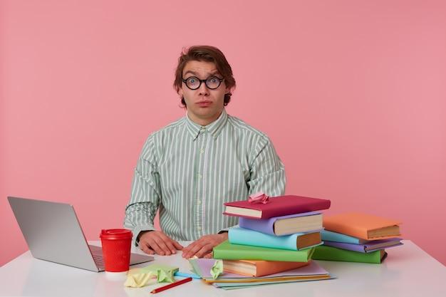 Foto van jonge trieste kerel in glazen, zit bij de tafel en werkt met laptop, in de camera kijken met ongelukkige uitdrukking, geïsoleerd op roze achtergrond.