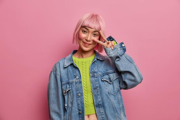 Foto van jonge verleidelijke vrouw met trendy roze kapsel, toont victroy gebaar over oog, stijlvolle denim jasje draagt, heeft plezier, poses