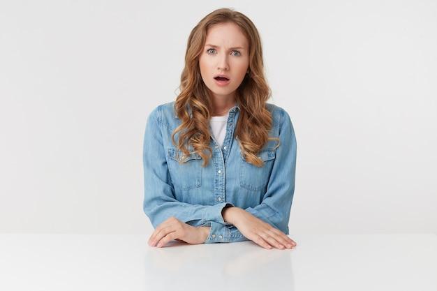Foto van jonge verontwaardigde blonde vrouw draagt in spijkeroverhemden, zittend aan de witte tafel, fronst en kijkt ontevreden, geïsoleerd op witte achtergrond.