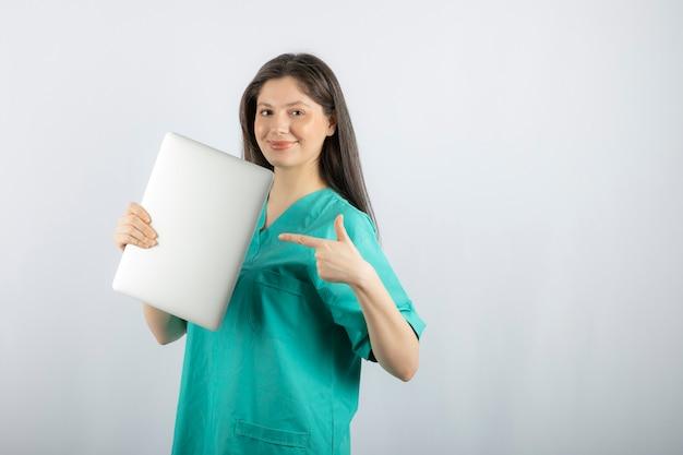 Foto van jonge verpleegster wijzend op laptop op wit.