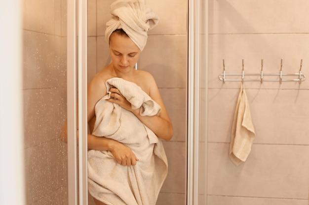 Foto van jonge volwassen slanke mooie vrouw die uit de douche stapt, staat en het lichaam afdroogt met een handdoek, 's ochtends onder de douche staat, netheid.