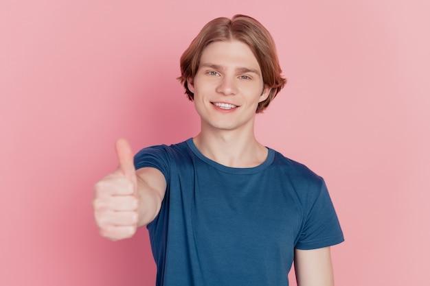 Foto van jonge vrolijke jongen, blije positieve glimlach, duim omhoog als cool advertentieadvies geïsoleerd over roze kleurachtergrond