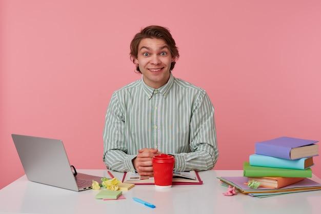 Foto van jonge vrolijke kerel met bril, zittend aan een tafel met boeken, werken op een laptop, kijkt naar de camera en glimlachen, geïsoleerd op roze achtergrond.
