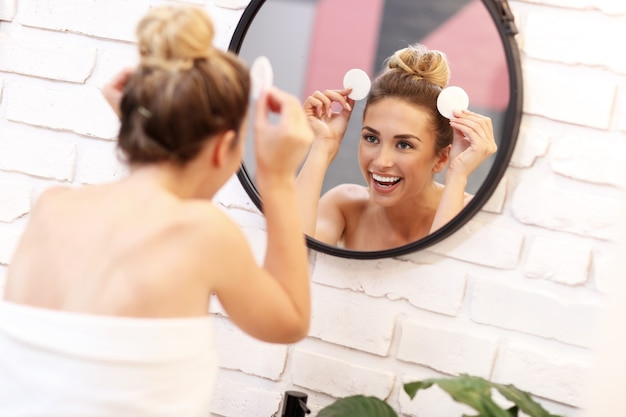 Foto van jonge vrouw die haar gezicht in de badkamerspiegel schoonmaakt