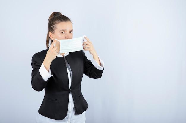 Foto van jonge vrouw die medisch masker op witte achtergrond draagt. hoge kwaliteit foto