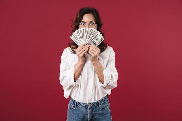 Foto van jonge vrouw geïsoleerd op rode muur met geld kegel gezicht.