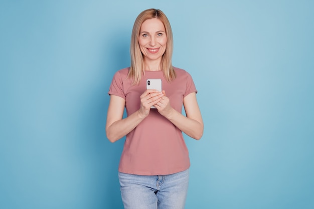 Foto van jonge vrouw gelukkig positieve glimlach gebruik mobiel internet online geïsoleerd over blauwe kleur achtergrond