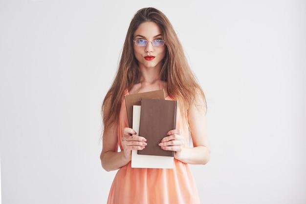 Foto van jonge vrouw in de glazen en rode lippen die de boeken houden.