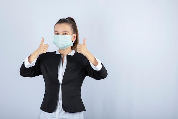 Foto van jonge vrouw in masker duimen opdagen op witte achtergrond. hoge kwaliteit foto