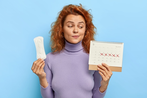 Foto van jonge vrouw kijkt naar periodekalender, controleert menstruatiedagen