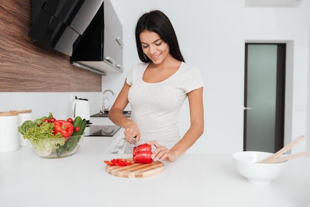 Foto van jonge vrouw koken in de keuken. producten bekijken.