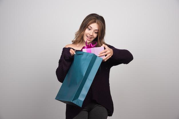 Foto van jonge vrouw met boodschappentassen.