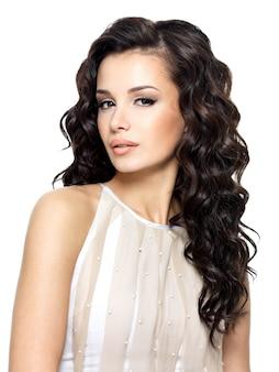 Foto van jonge vrouw met schoonheids lang krullend haar. mannequin poseren in studio.