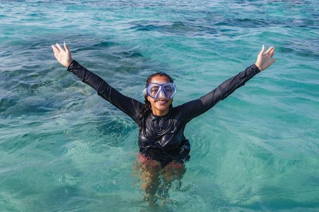 Foto van jonge vrouw op vakantie met zwembril in de zee.