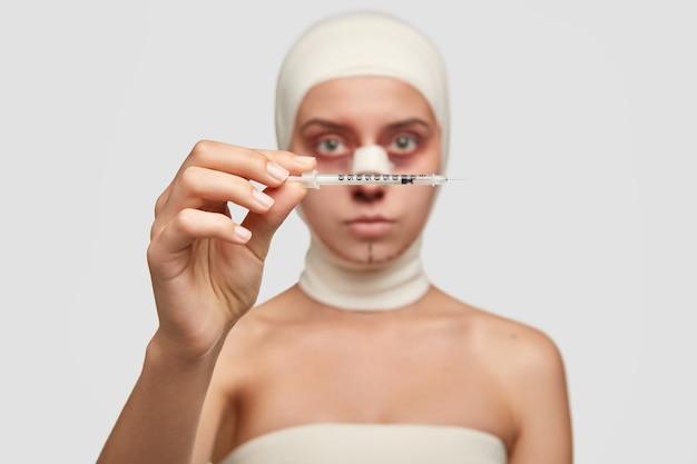 Foto van jonge vrouw patiënt in medisch verband, heeft kneuzingen na plastische operatie in kliniek, focus op naald