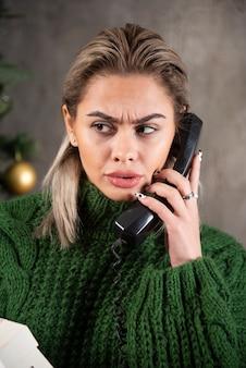 Foto van jonge vrouw praten over een zwarte telefoon