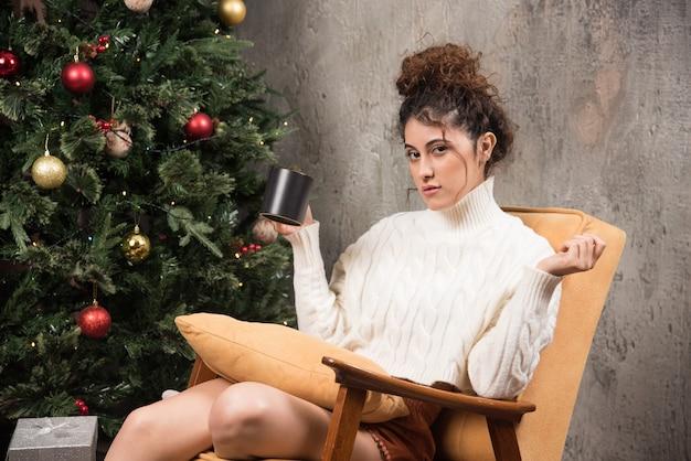 Foto van jonge vrouw zittend in een comfortabele stoel met een kopje drank