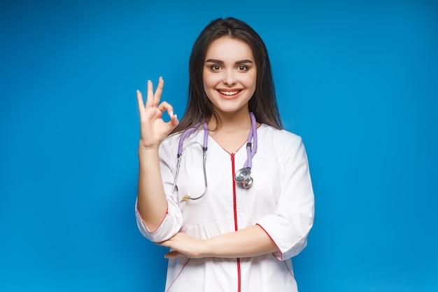 Foto van jonge vrouwelijke arts maakt okaysign, op blauw.