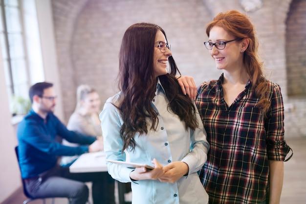 Foto van jonge vrouwelijke ontwerpers die op kantoor discussiëren