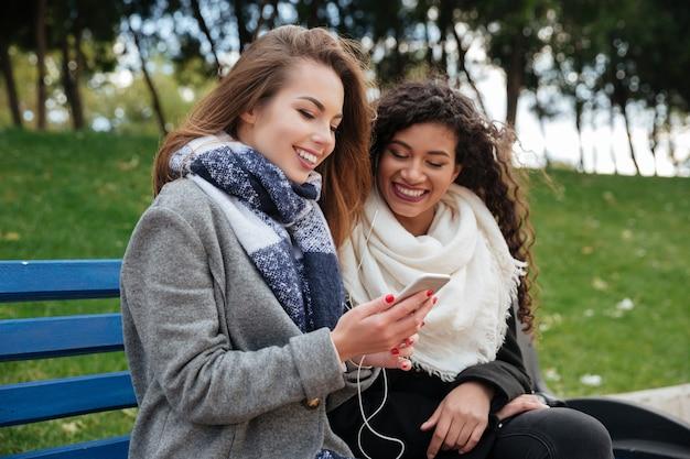 Foto van jonge vrouwelijke vrienden die naar elkaar glimlachen terwijl ze samen muziek luisteren op oortelefoons. telefoon kijken.
