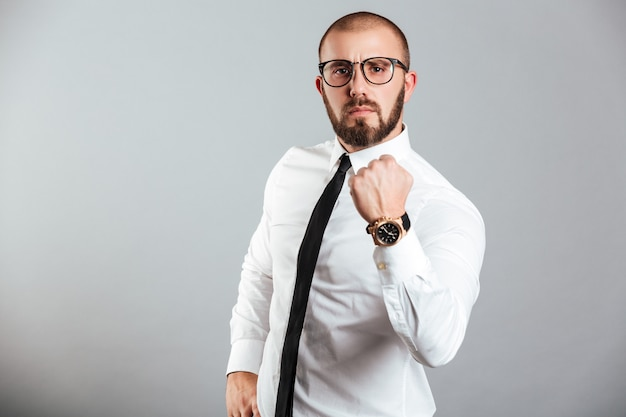 Foto van jonge zakenman in wit overhemd en oogglazen die stevig vuist tonen die sterkte of standvastigheid betekenen, die over grijze muur wordt geïsoleerd