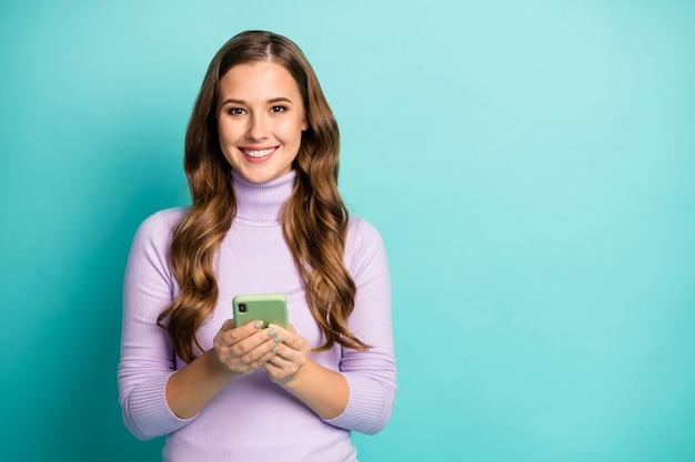 Foto van jongedame houd telefoon schrijven creatief populair blogbericht jeugdthema goed humeur slijtage paarse trui coltrui geïsoleerd groenblauw blauw pastelkleur