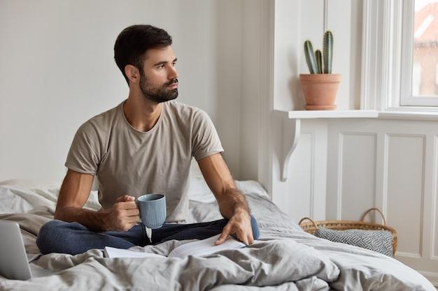 Foto van kalme knappe ongeschoren man leest graag bestseller, houdt mok met koffie of thee vast, zit gekruiste benen aan bed, denkt na over de levenssituatie, kijkt peinzend opzij. mensen en hobby-concept