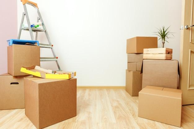 Foto van kartonnen dozen, ladders, pizza in nieuw appartement