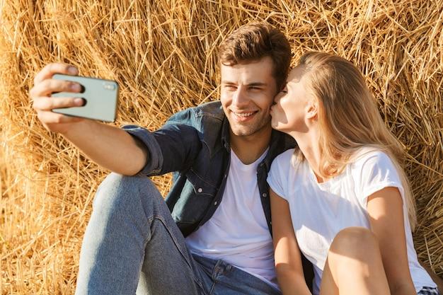 Foto van kaukasische paar man en vrouw selfie te nemen zittend onder grote hooiberg in gouden veld, tijdens zonnige dag