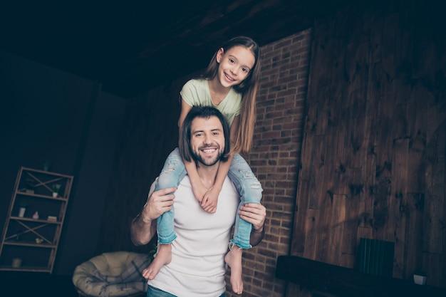 Foto van klein funky mooi meisje zit op schouders opgewonden knappe papa draagt dochter spelletjes spelen goed humeur vrije tijd doorbrengen