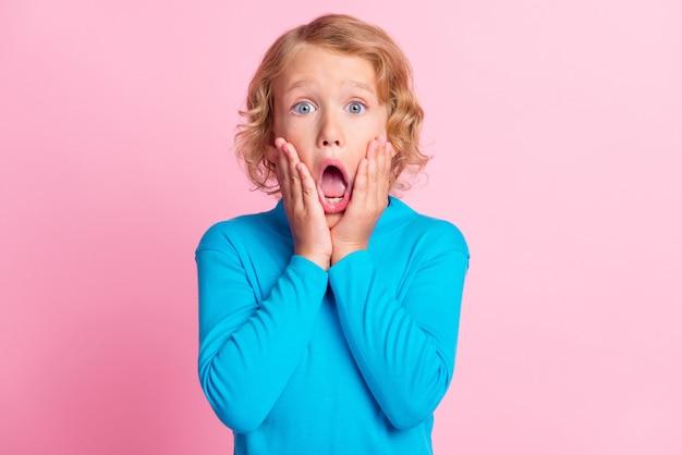 Foto van klein kind armen handpalmen jukbeenderen bang open mond draag blauwe coltrui geïsoleerde pastel roze kleur achtergrond