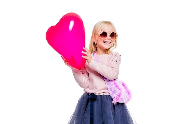 Foto van klein meisje in een roze trui en blauwe rok houdt een rode hartvormige ballon vast