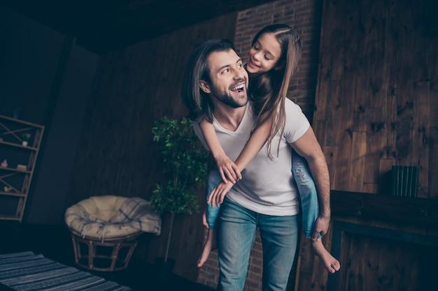 Foto van kleine grappige energieke meisje opgewonden knappe papa dragen dochter meeliften spelen spelletjes goed humeur vrije tijd doorbrengen