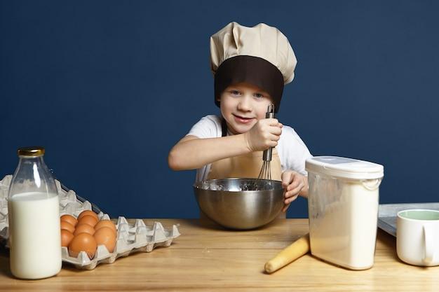 Foto van kleine jongen die schort en chef-kok glb draagt ?? ingrediënten in een metalen kom zwaait tijdens het koken van pannenkoeken, koekjes of ander gebak, staande aan de keukentafel met eieren, melk, bloem en deegroller