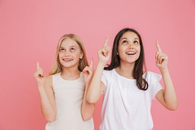 Foto van kleine meisjes van 8-10 jaar oud die vrijetijdskleding dragen die vingers naar boven richten op copyspace terwijl ze samen omhoog kijken, geïsoleerd op roze achtergrond